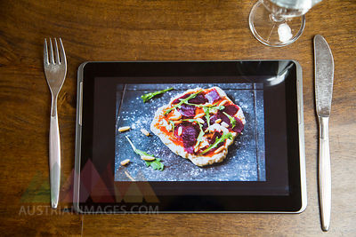 Digital tablet with food photography, glass  and cutlery on wood