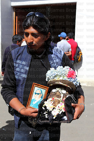 Devotee with photo and skull of his father, Ñatitas festival, La Paz, Bolivia