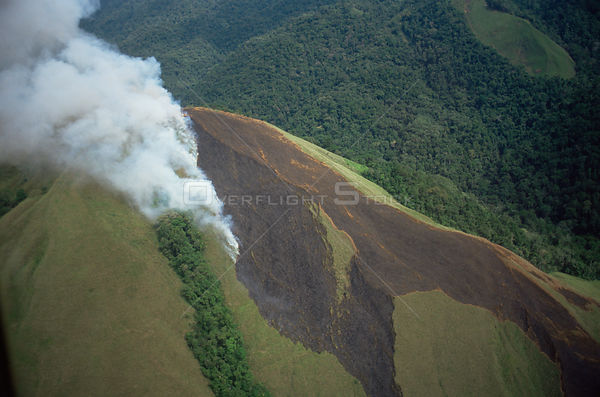 Aerial view of kunai grass burning, a traditional land management practice for agriculture, Papua New Guinea