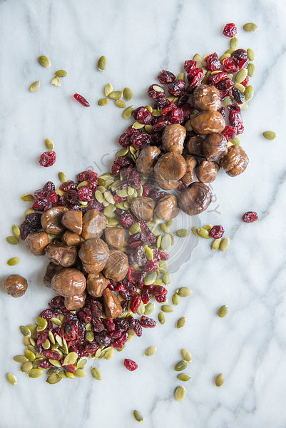 Roast chestnuts, cranberries and seeds on a marble chopping board.