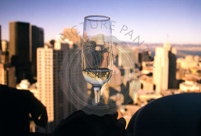 Sunset over San Francisco as seen from a rooftop bar.  Image of san francisco is reflected in the wine glass.