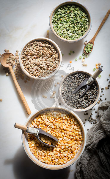 Brown lentil,French lentil Split dry green peas and Split chana dal in individual ceramic bowls on a marble backdrop on top d...