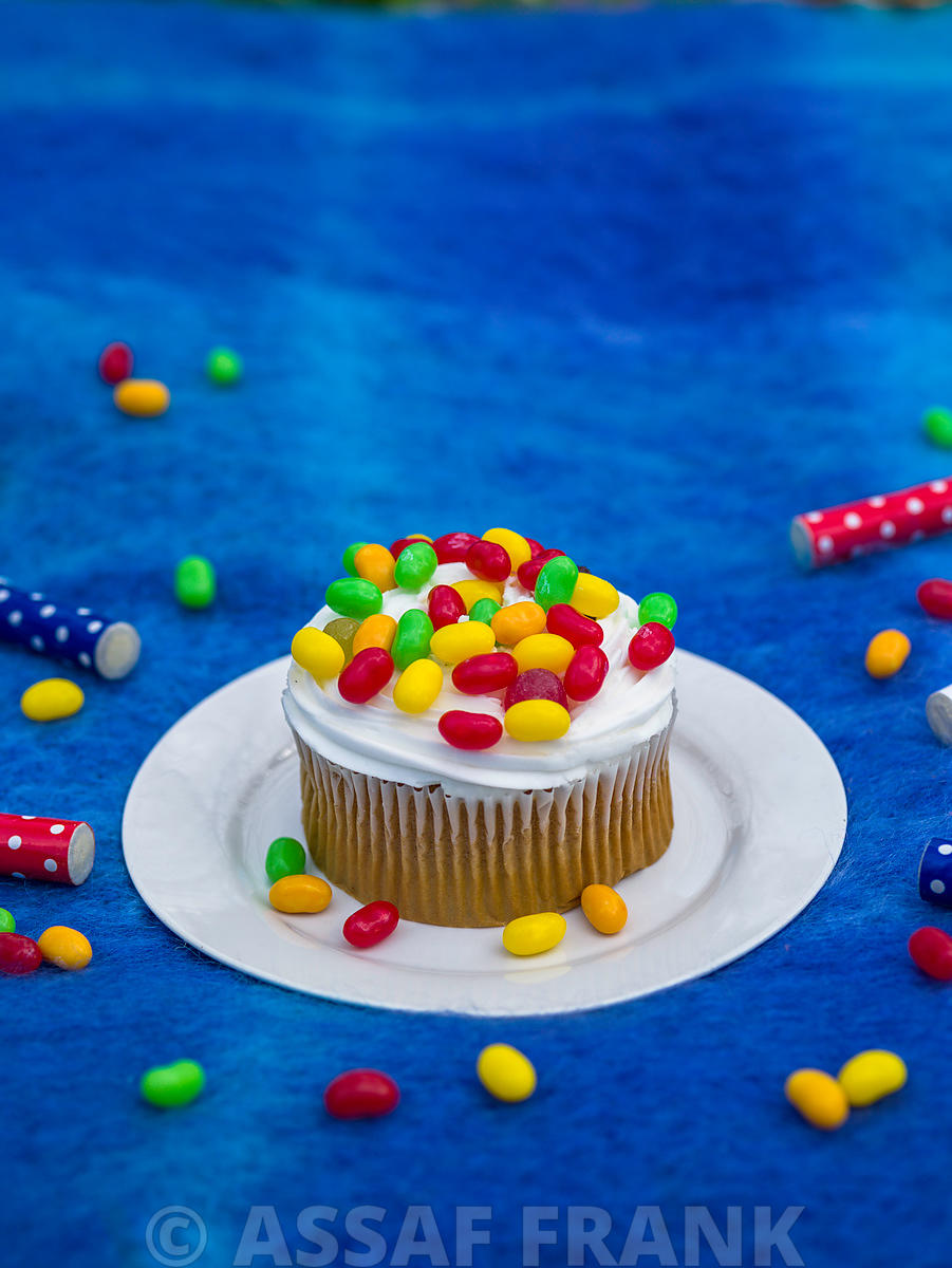 Cupcake with multi coloured sweets on blue background