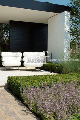 Terrasse contemporaine : Fauteuil Bibendum (collection Eileen Gray). Paysagiste : Paul Martin, Hampton Court, Angleterre