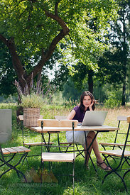 Germany, Hamburg, Woman using laptop in garden
