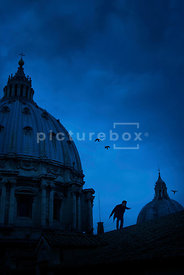 An atmospheric image of mystery man, with a gun, creeping over the fooftops in Rome, Italy.