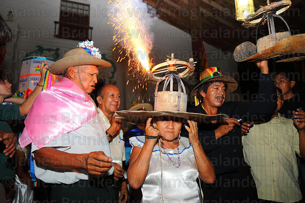 Woman with fireworks exploding on her hat about to run into crowd, San Ignacio de Moxos, Bolivia