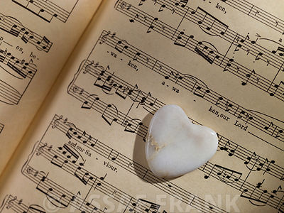 Heart shaped pebble on music book