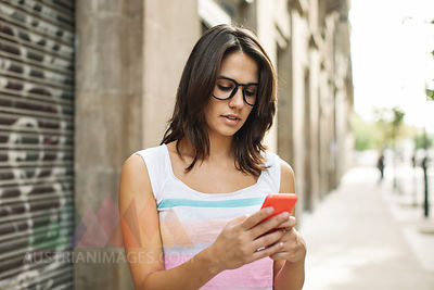 Young woman with smartphone reading SMS