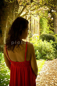 An atmospheric image af a mystery woman in a red dress, in a country garden.