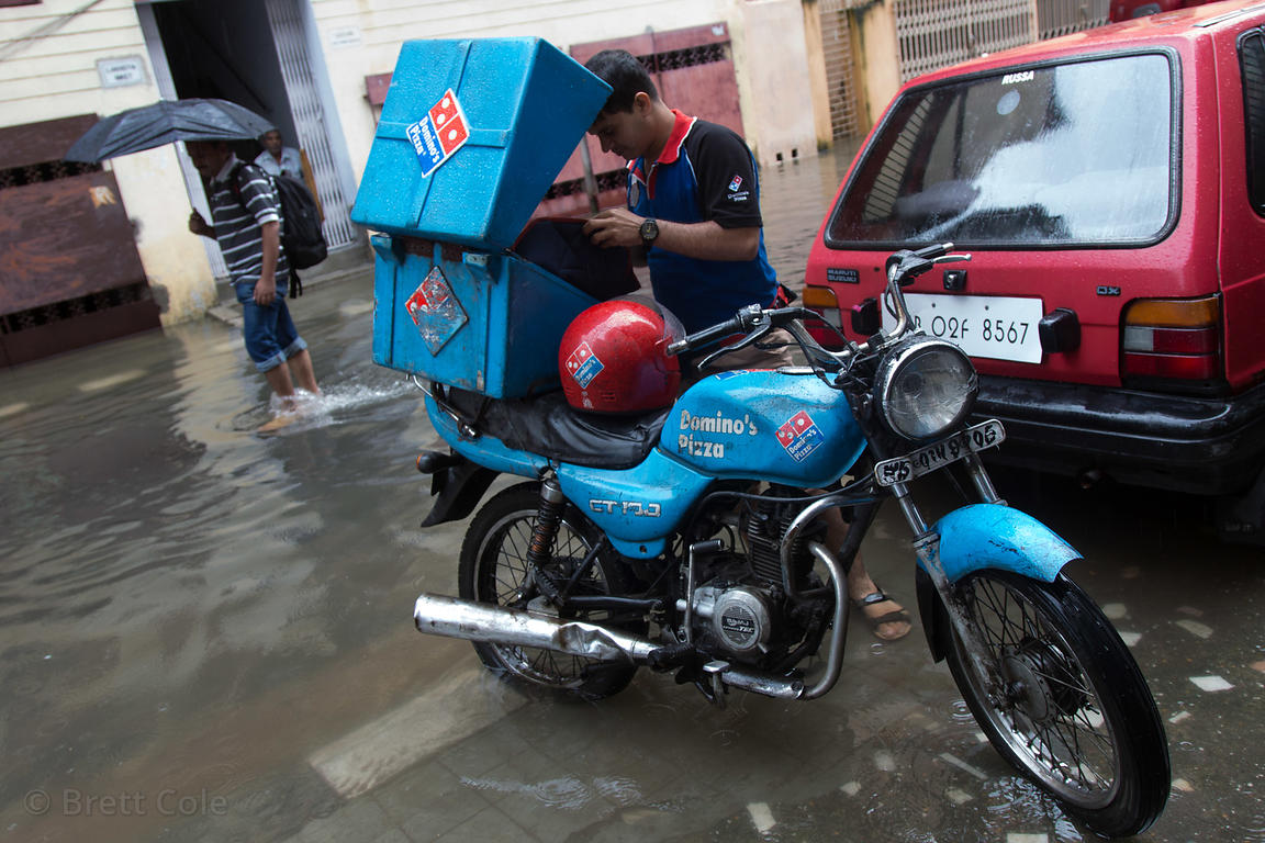 Domino's Pizza delivery motorcyle makes a delivery during monsoon flooding, Lake Gardens, Kolkata, India. Taken during the he...