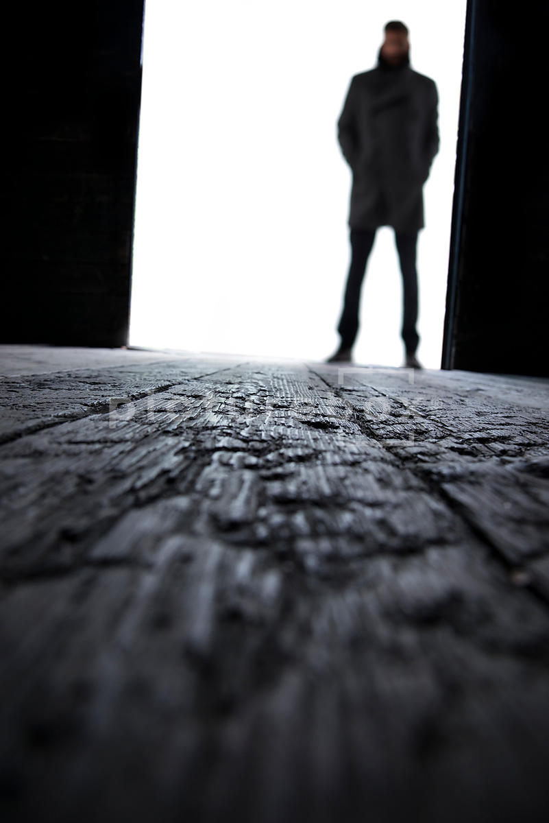 A blured sihouette of a man standing at a big open door to an old warehouse, looking at a focal point on the floor.