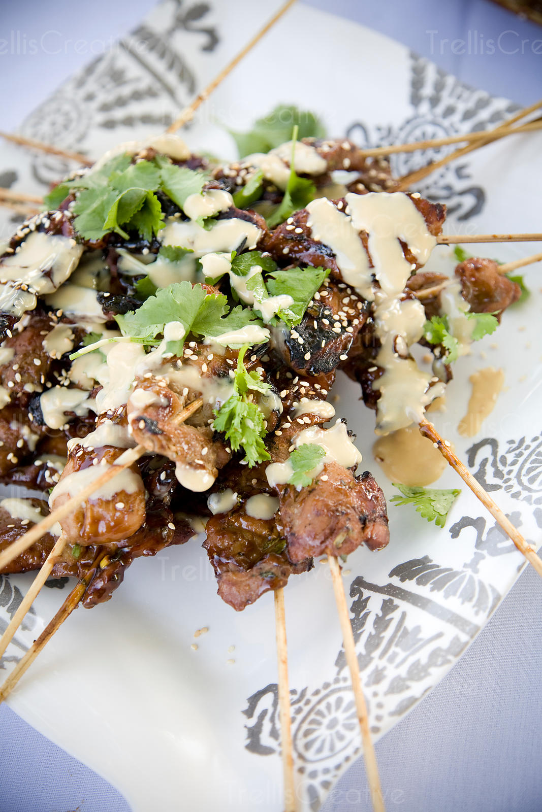 Chicken skewers with spicy thai peanut sauce garnished with sesame seeds