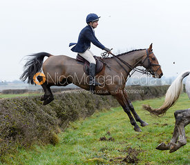 Clare Bell jumping a hedge on Greenall's