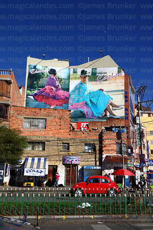Volkswagen Beetle driving past adverts for Cholita Collection fashion campaign on wall of building, El Alto, Bolivia