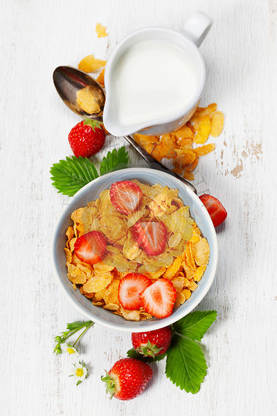 Breakfast with corn flakes, milk  and strawberry