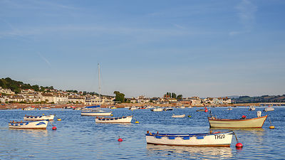 Boats at sunrise looking across Teign estuary to Shaldon at The Point, Teignmouth, Devon, UK