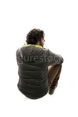 A man in outdoor clothing crouching or sitting on a rock looking down – shot from above.
