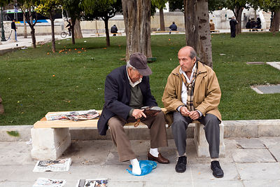 Greece - Athens - An old man shows another the sole of his shoe as they sit on a bench in Syntagma Square
