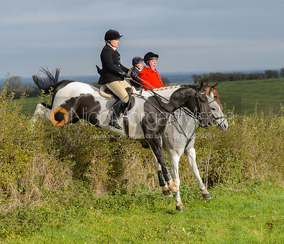 (L-R) Georgie Mason, Tom Kingston, Aurelia Rupert jumping a hedge near Clawson Thorns