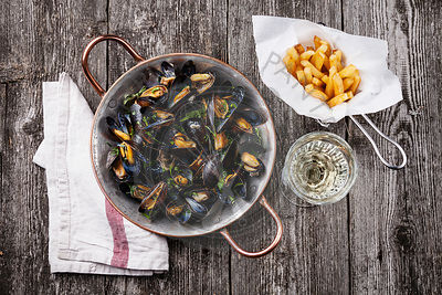 Mussels, french fries and wine on dark wooden background