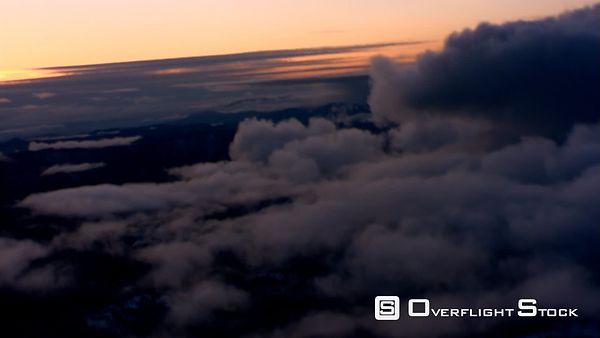 Evening flight over sparse cloud layer above mountainous terrain, passenger POV
