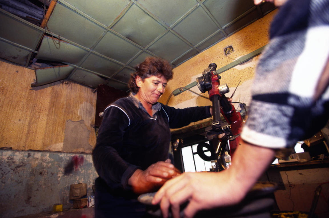 Albania - Skhoder - Lula Ivanaj at work in her garage where she works as a mechanic