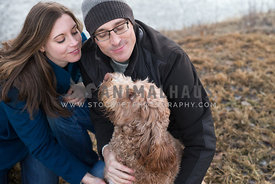 young couple cuddling labradoodle dog