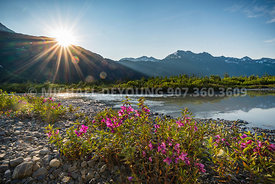 Sun setting behind mountain ridge at the outlet of Spencer Lake - Spencer Glacier, Alaska