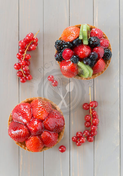 Two pastry tarts. Strawberry tart and a summer fruit tart.