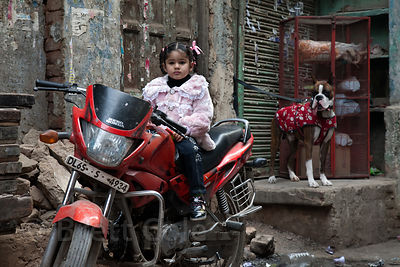 Girl on a motorcycle and a brindle boxer dog in the Paharganj area of Delhi, India