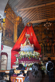 Devotees praying to figure of Virgen del Carmen inside church, Paucartambo , Peru