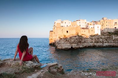 Woman looking at the old town, Polignano a mare, Apulia, Italy