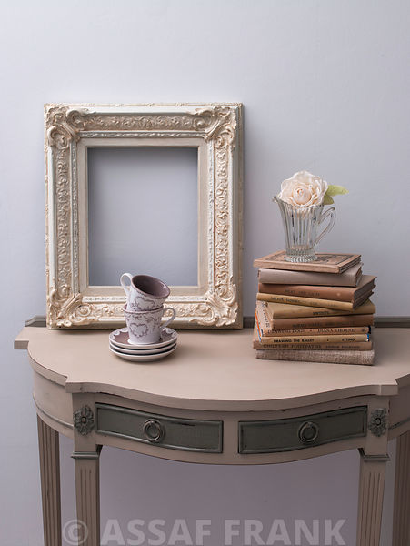 Side table with photoframe, coffee cups, books and flower vase