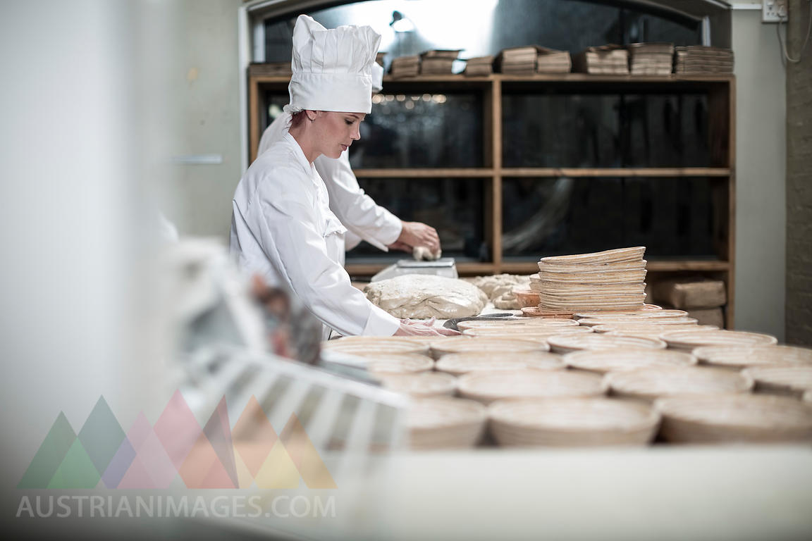 Female baker preparing ceramic bowls for baking bread