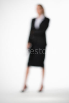 A blurred, standing blonde business woman – shot from mid level.