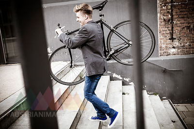 Young businessman carrying bicycle across steps, Munich, Bavaria, Germany