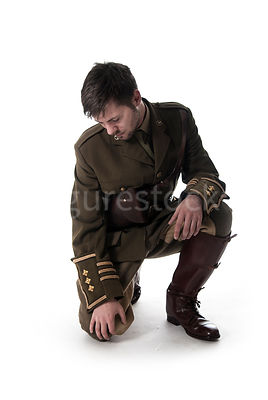 A weary first world war British officer crouching down – shot from low level.