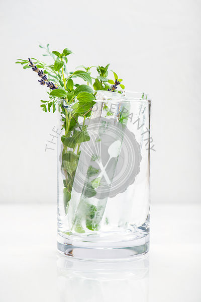 A large glass with artisan ice cubes and freshly cut herbs.