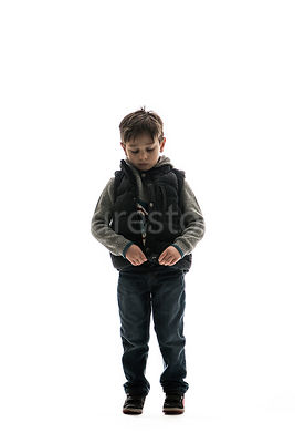 A boy looking sad and playing with his coat - shot from mid level.
