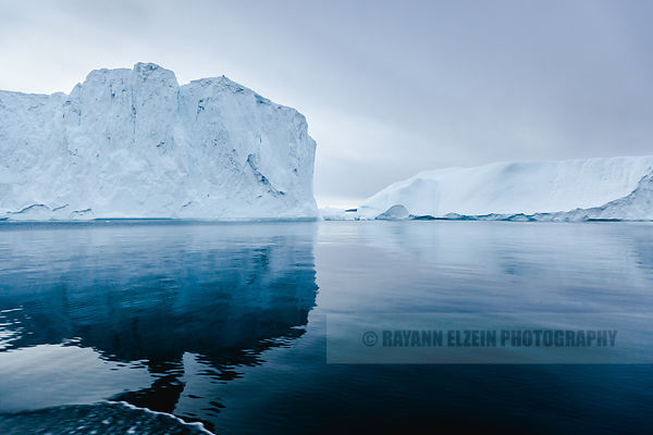 A large iceberg reflecting in very calm water in the Unesco Ilulissat Icefjord