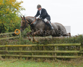 Nick  Wright jumping a hedge near Wilson's - The Cottesmore at Langham.