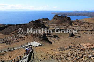 Looking over the walkway and volcanic spatter cones of Bartolome Island to Santa Cruz in the distance (left) and the lava flo...