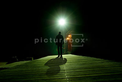 An atmospheric image of a mystery man walking along an old Jetty towards a cabin.
