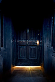 An atmospheric image of a spooky old door with light coming though the crack at the bottom and the keyhole.