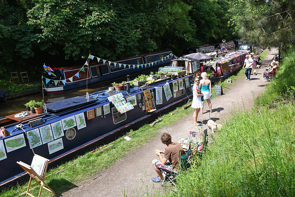 Visitors, on the warmest day of the year so far, enjoy seeing the narrowboats moored close to the Audlem Music Festival in Au...