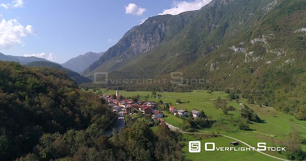 Mountain town, C4K aerial rising drone view of a small alpine town, near soca river, on a sunny summer day, in the Julian alp...