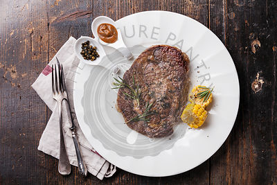 Grilled Black Angus Steak Ribeye and Pepper sauce on white plate on wooden background