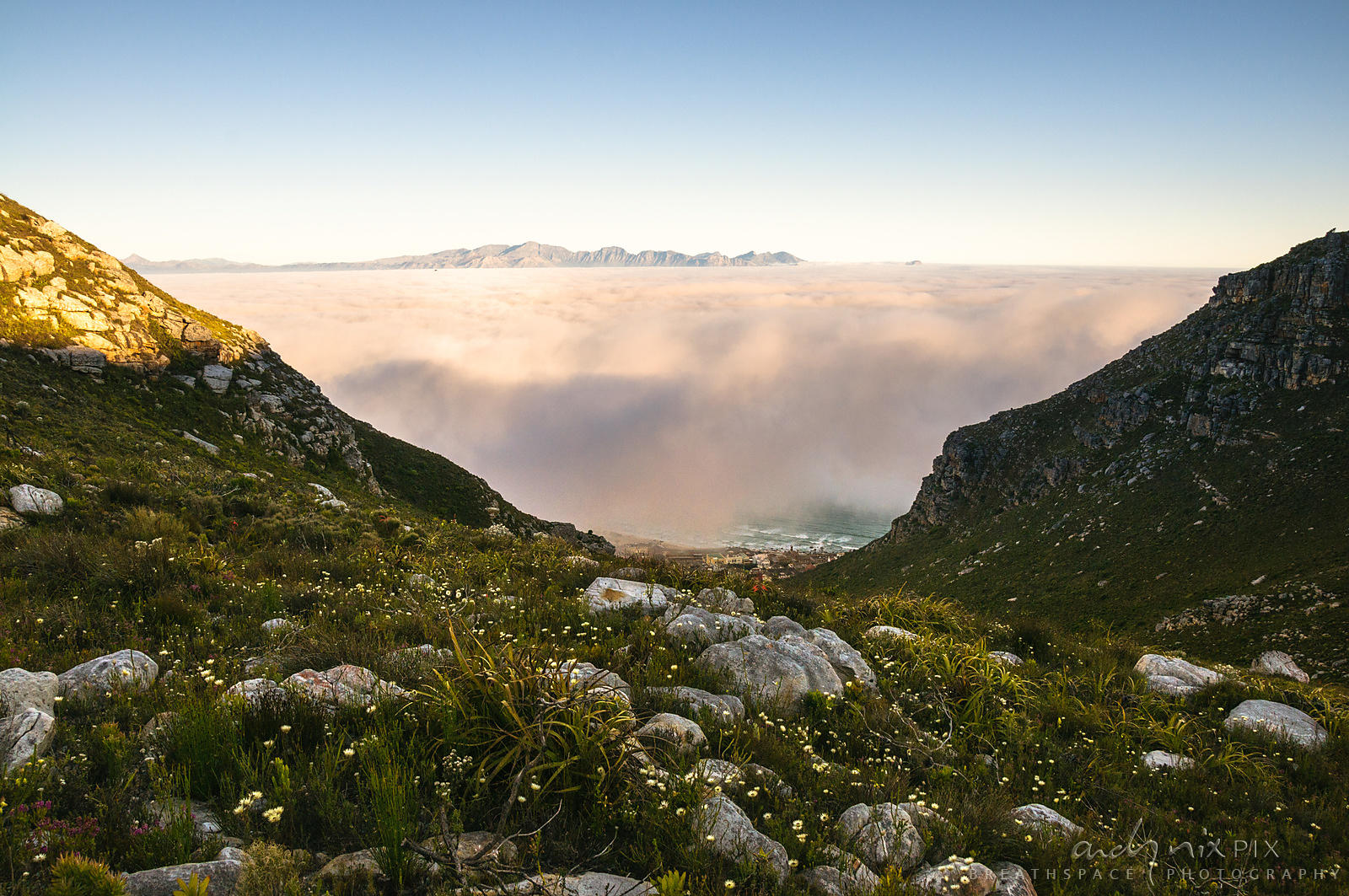 Fog over False Bay viewed from Muizenberg Peak (Farmer Peck's Valley) with sea and village at foot of mountain visable below ...