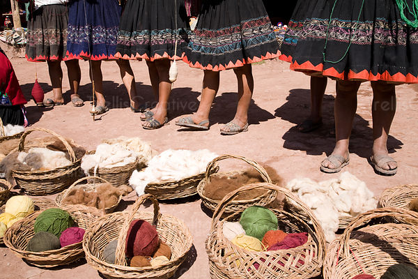 Kechwa women standing with alpaca yarn in the village of Qeshwarani, Peru